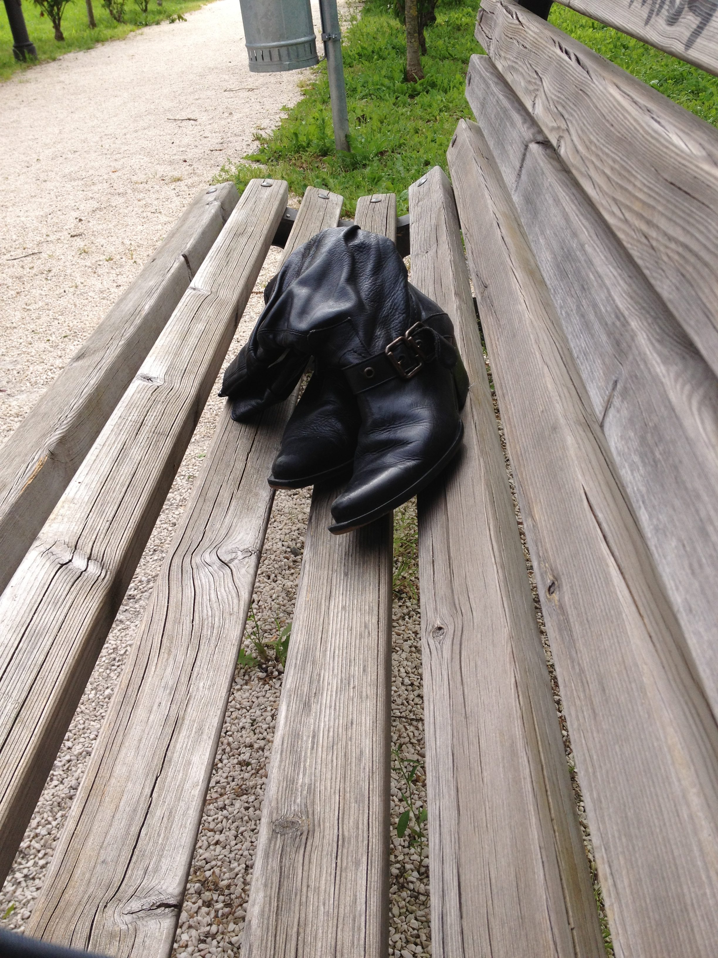 stivali neri abbandonati su una panchina